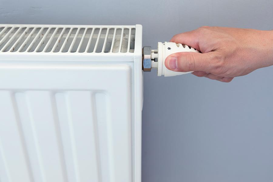 persona girando la rueda del radiador para poner la calefacción